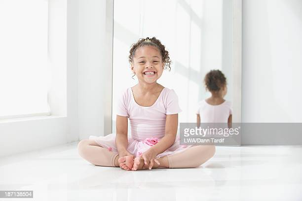 Mixed race girl stretching before ballet class