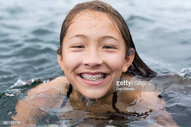Mixed race girl swimming outdoors