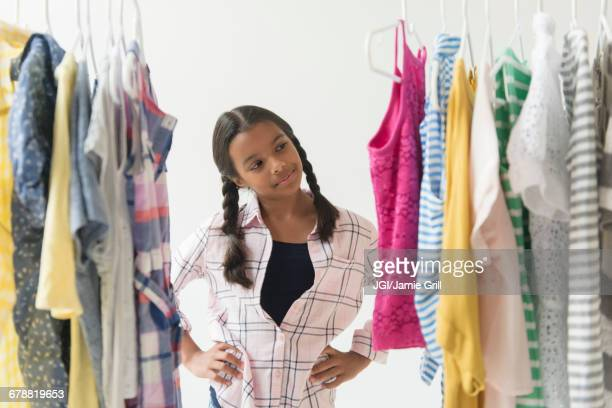 Mixed Race girl thinking about clothing on rack
