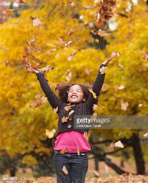 Mixed race girl throwing autumn leaves