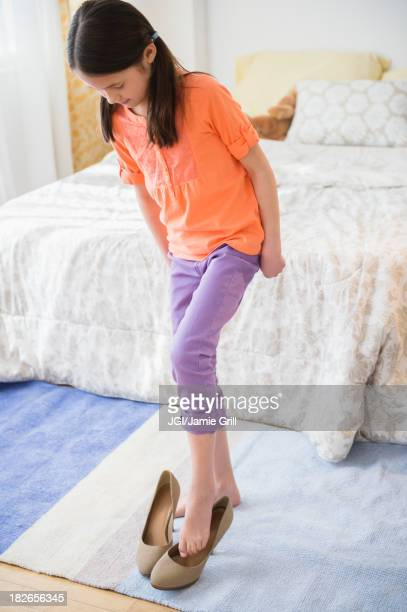 mixed race girl trying on mother's heels - little girl in high heels stock photos and pictures