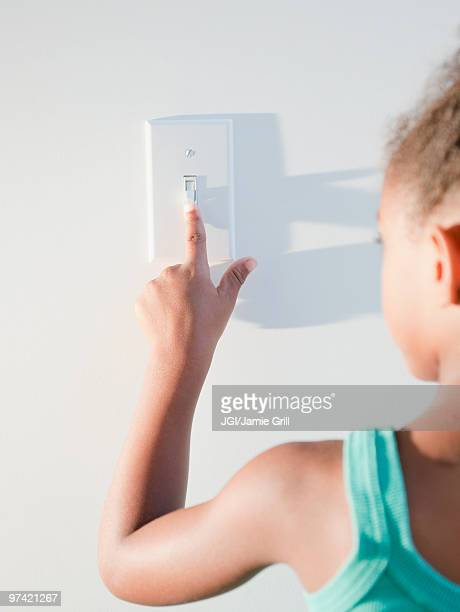 Mixed race girl turning off light