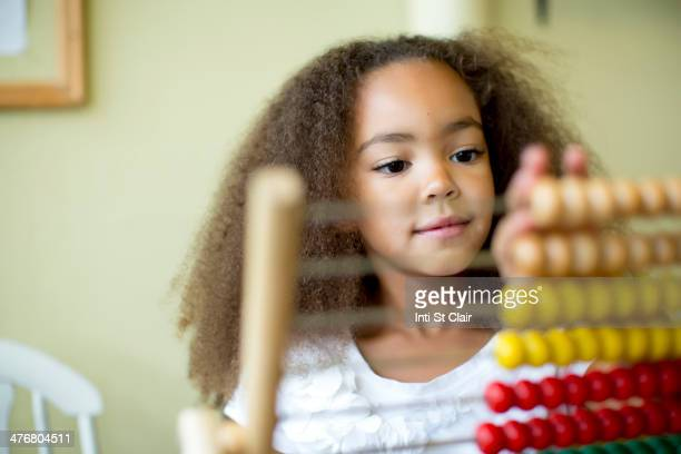 Mixed race girl using abacus