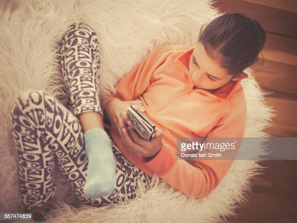 mixed race girl using cell phone on in furry chair - hairy little girls stock photos and pictures