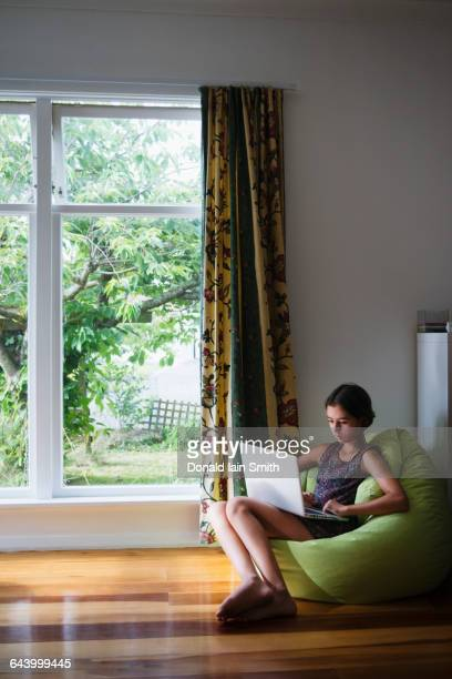 Mixed race girl using digital tablet in beanbag chair