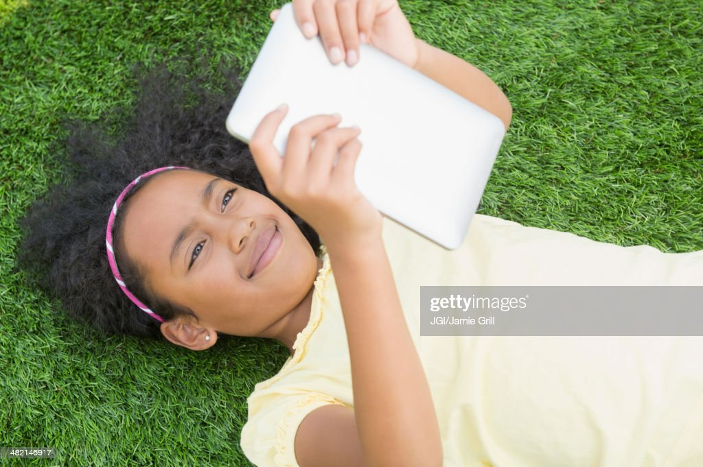 Mixed race girl using digital tablet in grass : Stock Photo