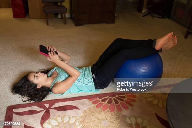 mixed race girl using digital tablet on floor - barefoot feet up lying down girl stock photos and pictures