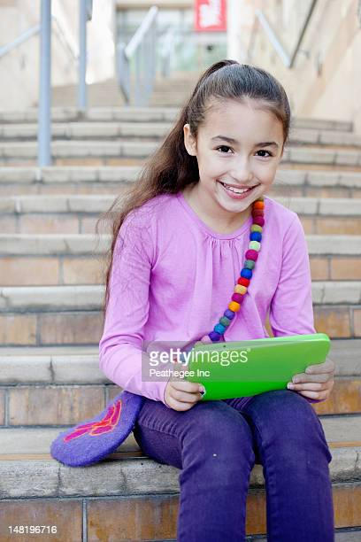 Mixed race girl using digital tablet on staircase