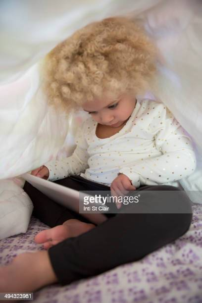 Mixed race girl using digital tablet under covers
