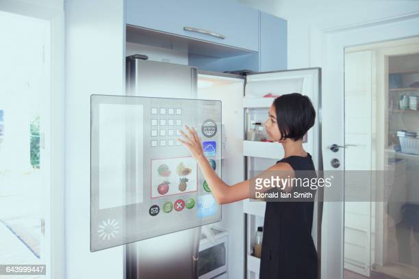 mixed race girl using hologram refrigerator touch screen in kitchen - 近未来的 ストックフォトと画像