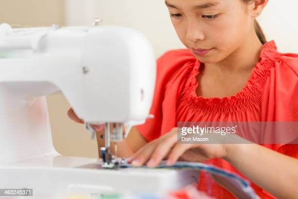 Mixed race girl using sewing machine