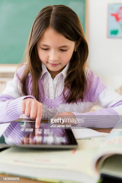 Mixed race girl using tablet computer in class
