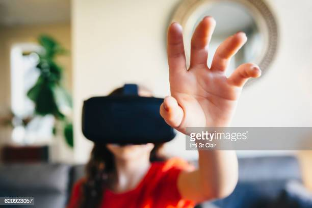 Mixed race girl using virtual reality goggles