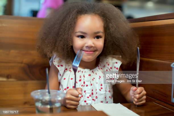 Mixed race girl waiting for food in restaurant