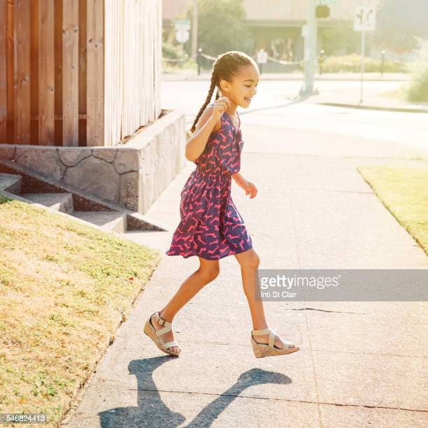 Mixed race girl walking on neighborhood sidewalk