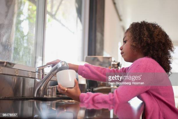 Mixed race girl washing dishes