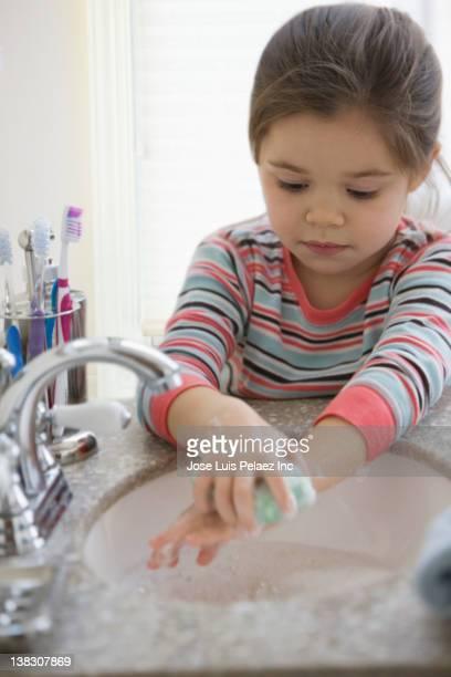 Mixed race girl washing hands