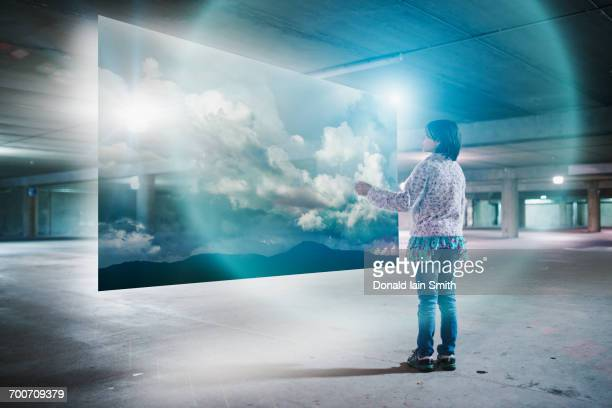 Mixed Race girl watching clouds on virtual screen in parking garage