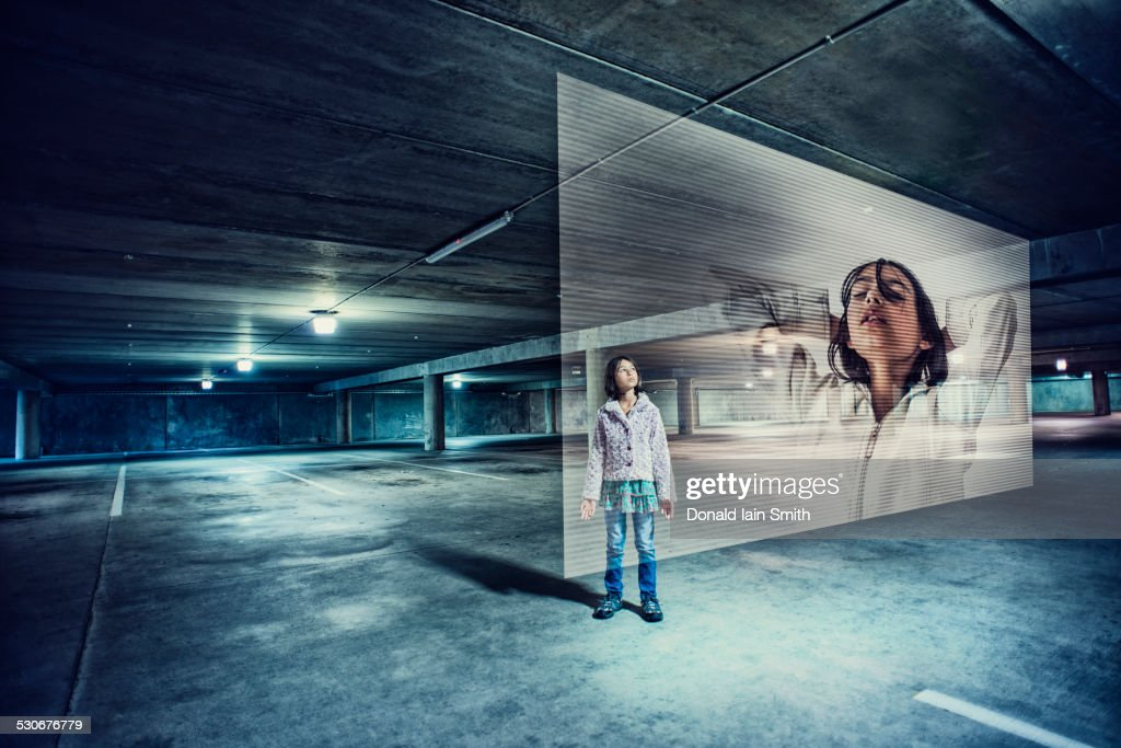 Mixed race girl watching holographic screen in parking lot : Stock Photo