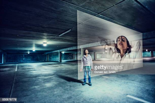 Mixed race girl watching holographic screen in parking lot