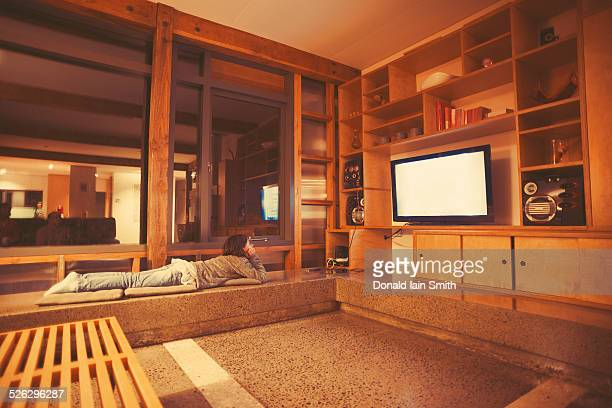 Mixed race girl watching television in modern living room