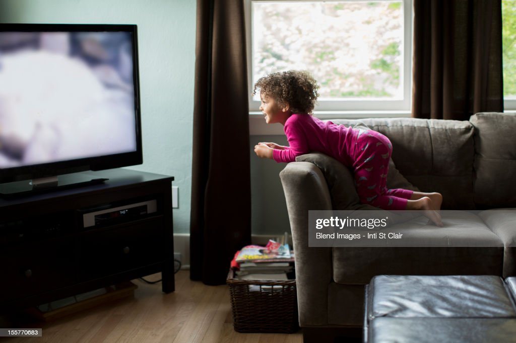 Mixed race girl watching television : Stock Photo