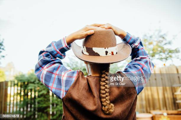 Mixed race girl wearing cowboy costume in backyard