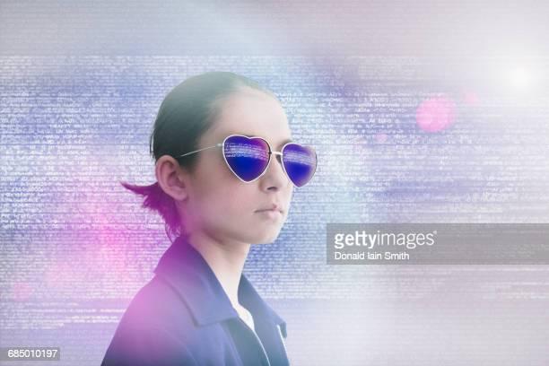 Mixed Race girl wearing heart-shape sunglasses in data cloud