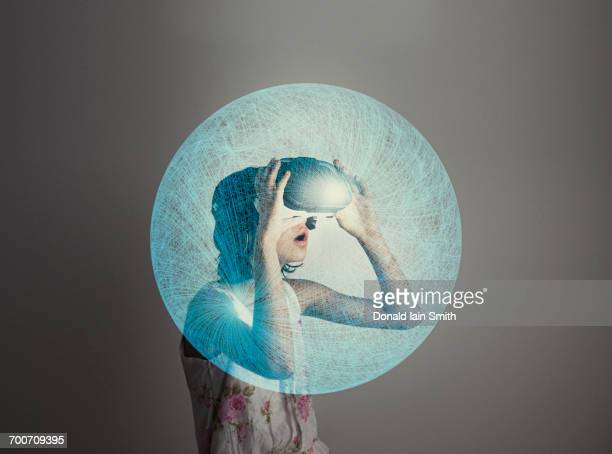 Mixed Race girl wearing virtual reality goggles in blue sphere
