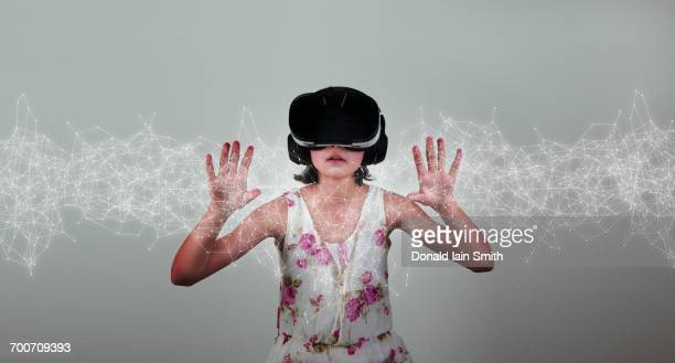Mixed Race girl wearing virtual reality goggles