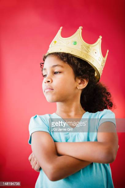 mixed race girl with arms crossed wearing crown - children only stock pictures, royalty-free photos & images