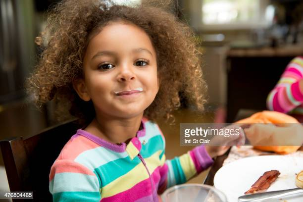 Mixed race girl with milk mustache at table