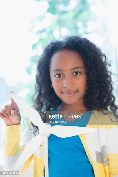 Mixed race girl with model wind turbine