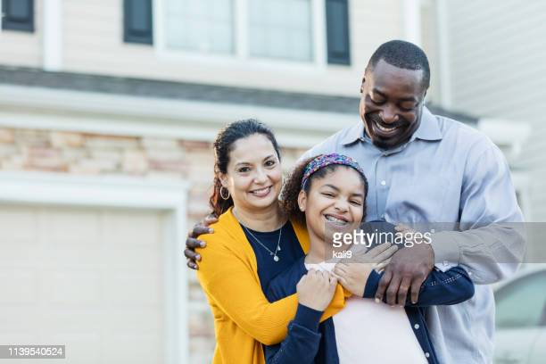 mixed race girl with parents outside home - in front of stock pictures, royalty-free photos & images
