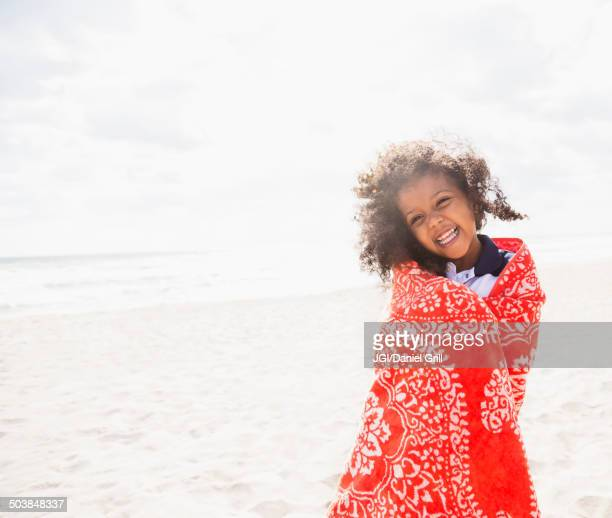 Mixed race girl wrapped in towel on beach