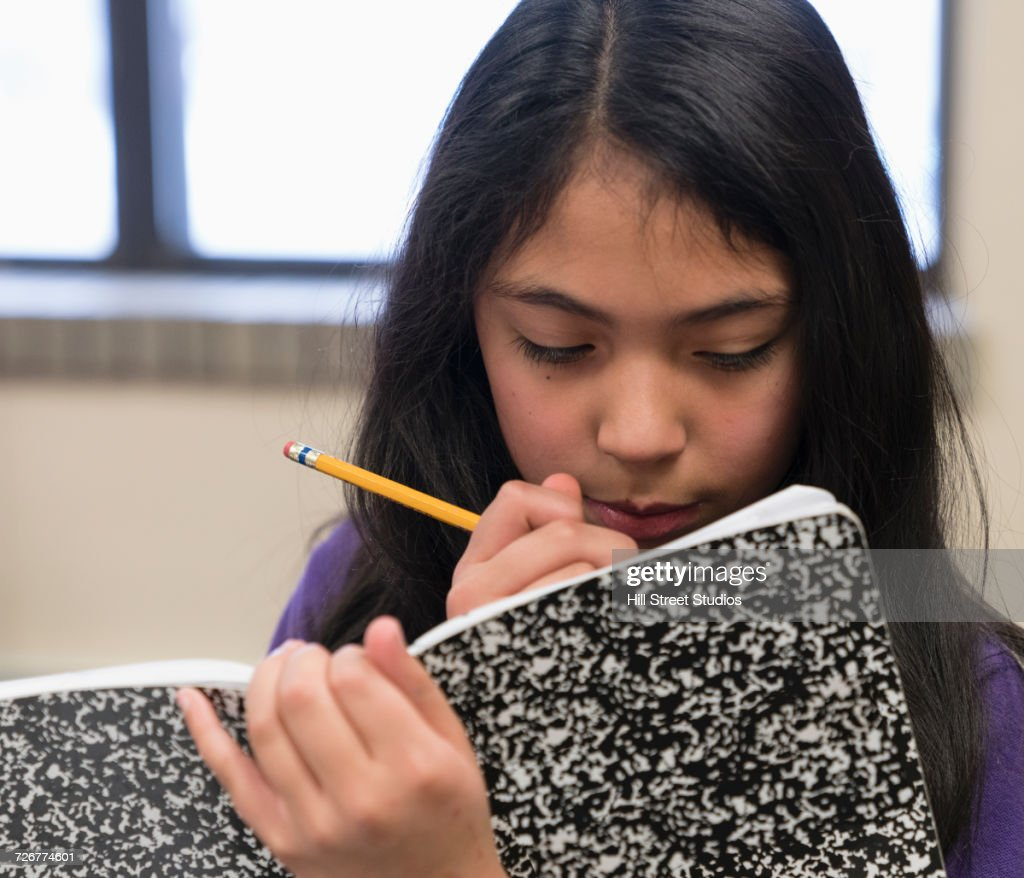 Mixed Race girl writing in notepad with pencil : Stock Photo
