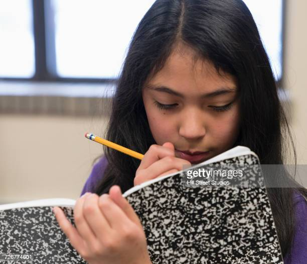 Mixed Race girl writing in notepad with pencil