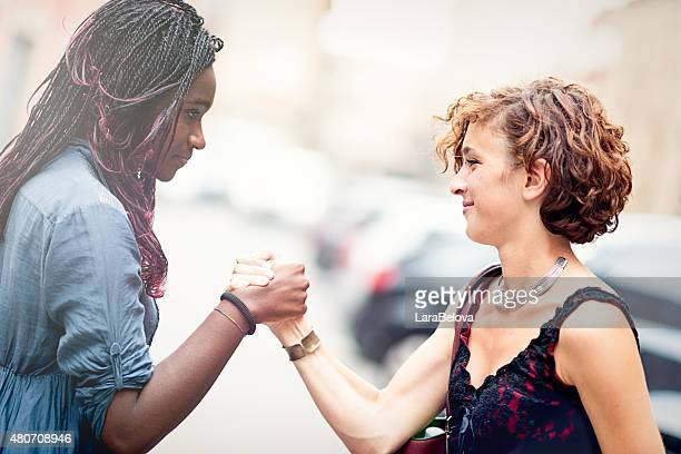 Mixed race girlfriends making a sign of forgiveness
