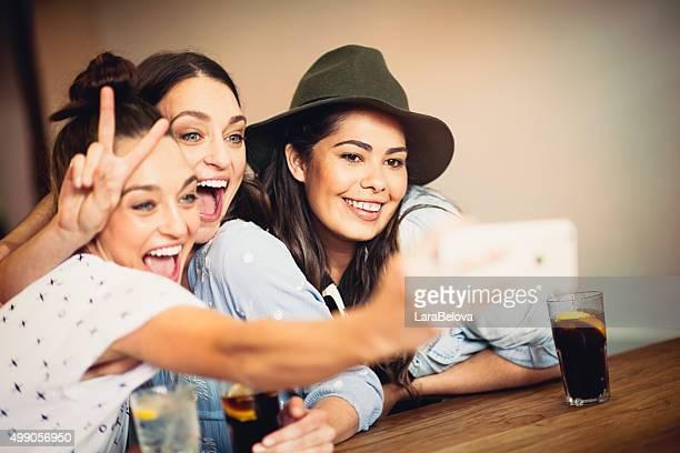 Mixed race girlfriends taking selfie in pub