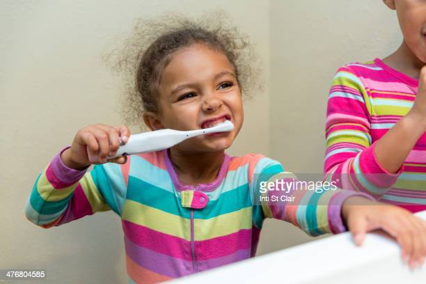 Mixed race girls brushing their teeth