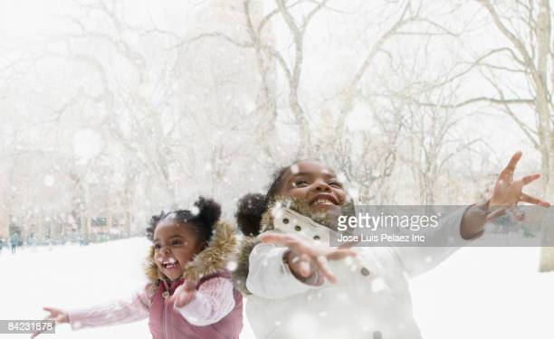 mixed race girls catching snowflakes - black coat stock pictures, royalty-free photos & images
