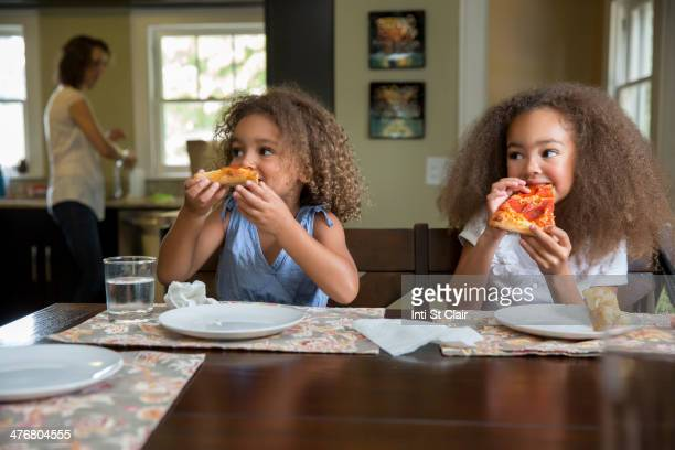 Mixed race girls eating pizza at table