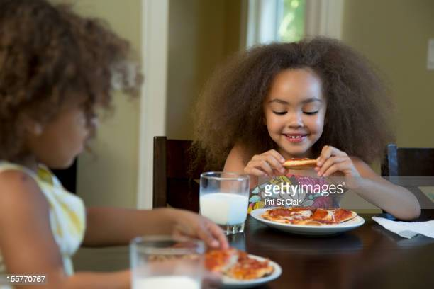 Mixed race girls eating pizza