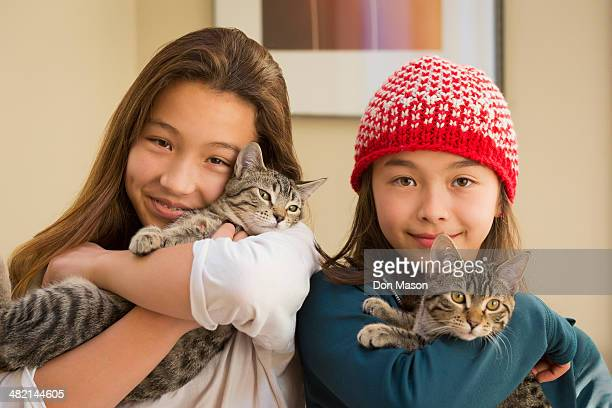 Mixed race girls holding kittens
