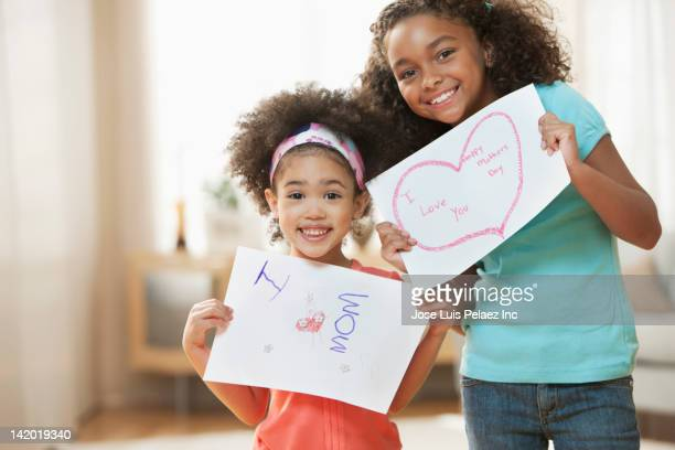 Mixed race girls holding Mother's Day cards