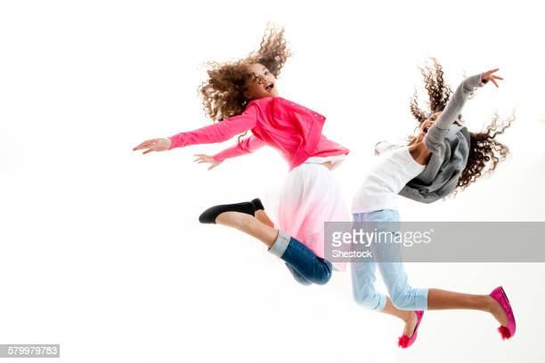Mixed race girls jumping for joy