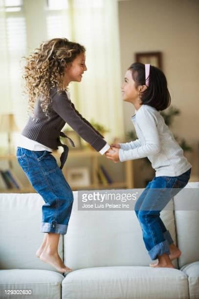 Mixed race girls jumping on sofa