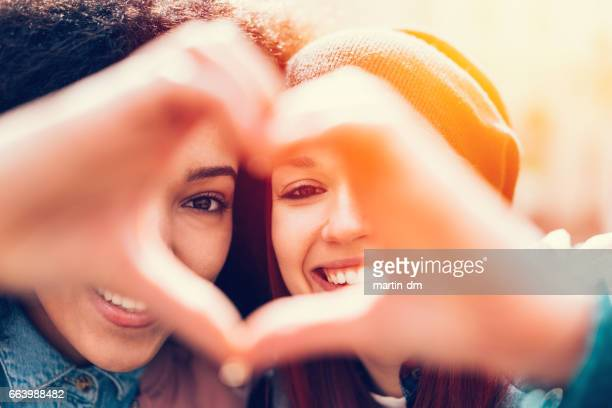 Mixed race girls making heart symbol with hands