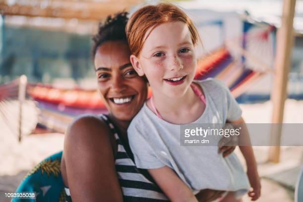meninas de raça mista de férias de praia - dama de companhia - fotografias e filmes do acervo