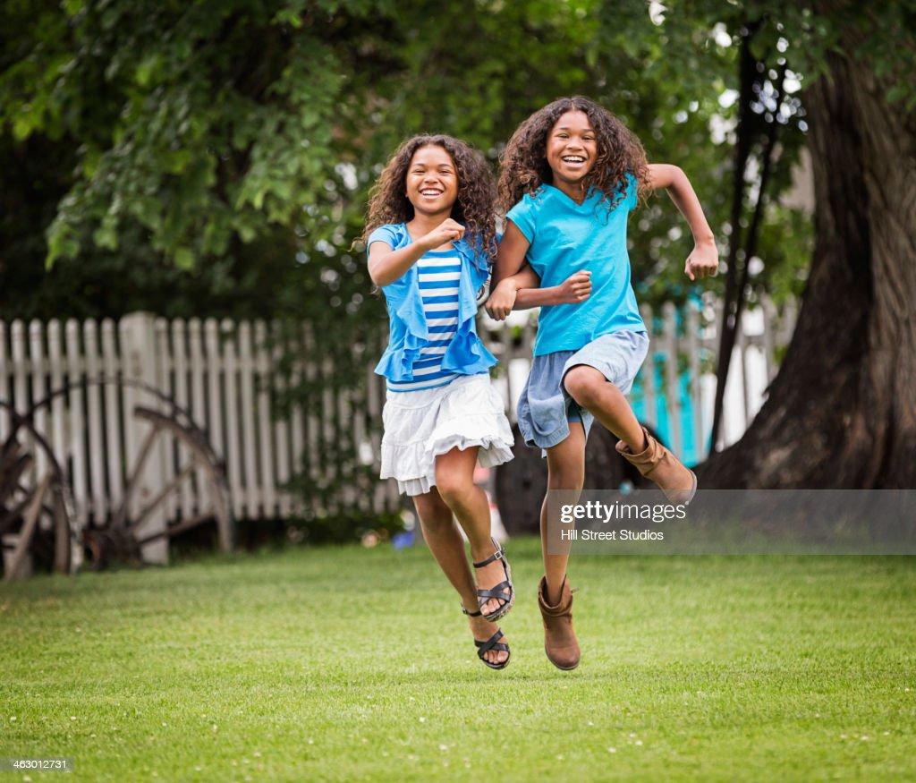 Mixed race girls playing in backyard : Stock Photo